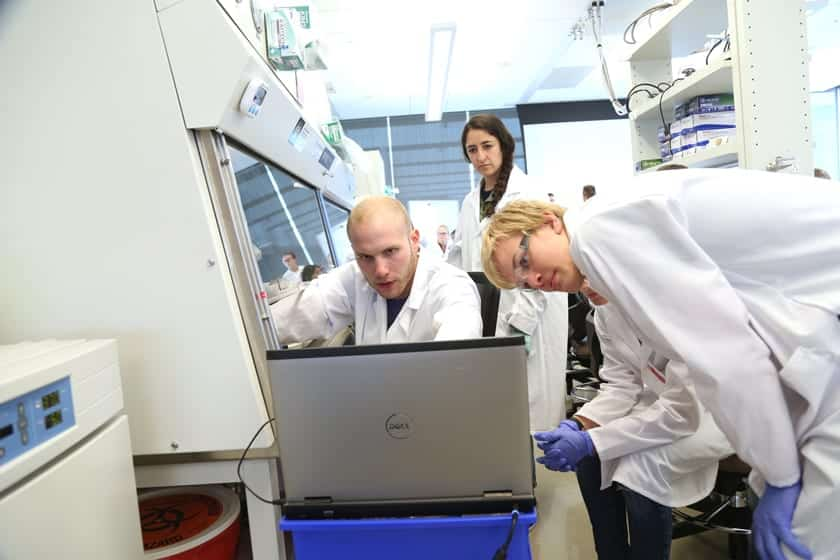 Daniel Gil, a graduate researcher in the Multiscale Imaging in Medicine Lab led by Melissa Skala, manipulates a microscope under the hood while the cellular image projects on a laptop. The Skala Lab led a multi-day research project with the campers looking at treatments for cancer cells.