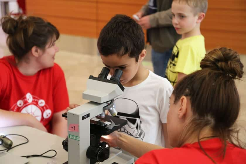 A young visitor looks at cell samples under a microscope during a Science Expeditions event at the Discovery Building. The activity was developed as part of the Discovery Incubator program.