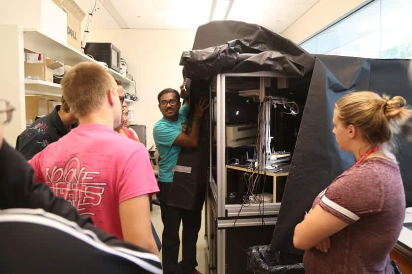 Sailendharan Sudakaran from the Vetsigian group at the Wisconsin Institute for Discovery shows off a microscope built in-house for studying microbial interactions. Campers prepared petri dishes of bacteria that they then viewed under this microscope.