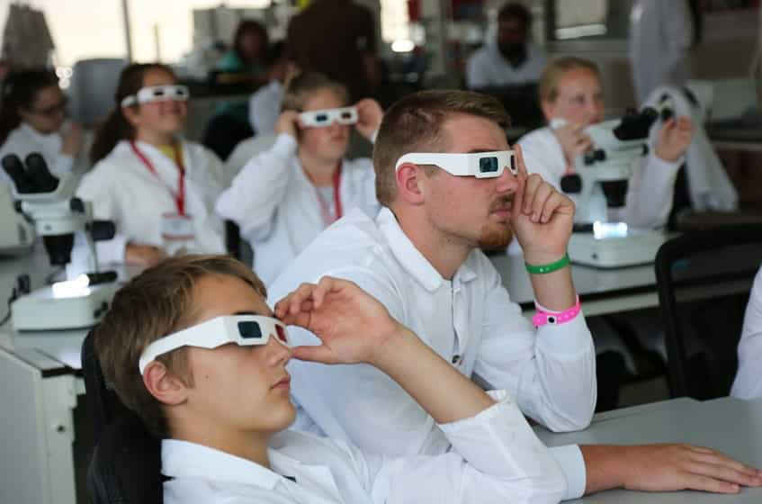 Campers wear 3-D glasses to view scientific images created with a lightsheet microscope. Activity presented by the Jan Huisken Lab.